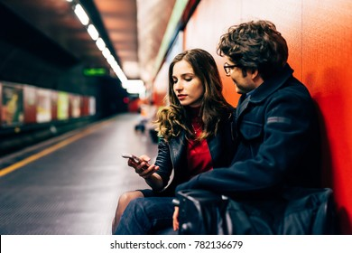 Young beautiful couple in love using smart phone together in the underground - interaction, love, technology concept