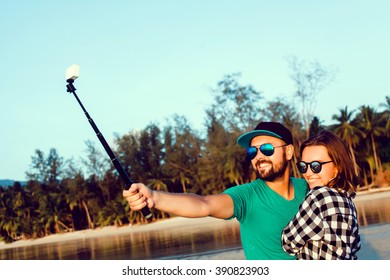 young beautiful couple making selfie photo on a selfie stick, hipsters, lovers together smile laugh photos on gopro, action camera, take pictures and shoot video at the beach,outdoor portrait,close up