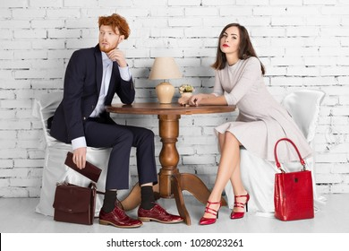 young beautiful couple. Man and woman sits in a cafe at a wooden old table.  A man in a suit is holding a purse   Gorgeous woman is holding her hands on the table background white brick wall Red shoes