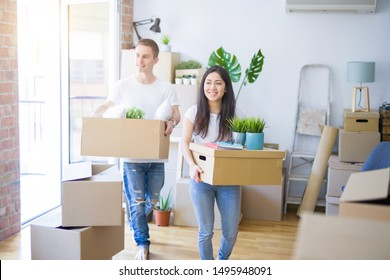 Young beautiful couple moving cardboard boxes at new home