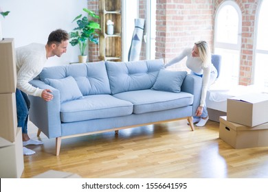 Young beautiful couple moving sofa at new home around cardboard boxes