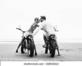 Young beautiful couple on motorcycles kissing on the beach, outdoor portrait, bearded guy, blonde girl, travel together, ocean, sea