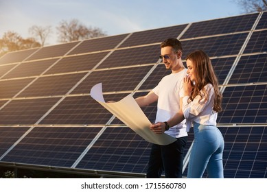 Young beautiful couple on a sunny day is standing by a solar module and looking into a big white paper plan, thinking about future, concept of bright future