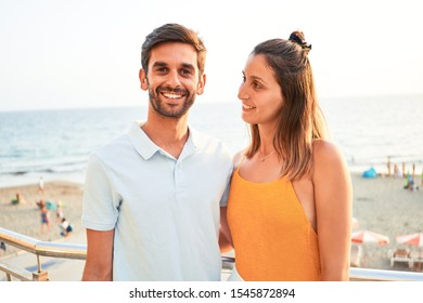Young beautiful couple on vacation smiling happy and confident. Standing with smile on face hugging at the beach