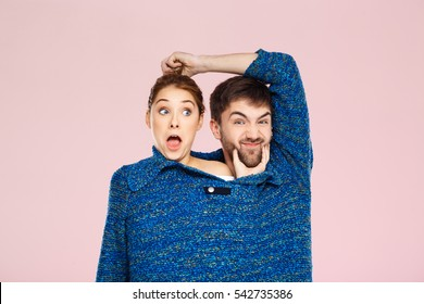 Young beautiful couple in one blue knitted sweater posing smiling having fun over light pink background.