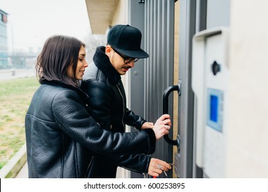 Young beautiful couple opening front door of their new house - love, relationship, couple concept