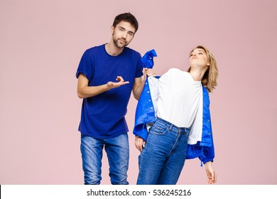 Young beautiful couple posing having fun  over light pink background.