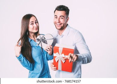 Young beautiful couple with present isolated. To give gifts.