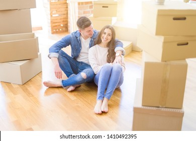 Young beautiful couple relaxing sitting on the floor around cardboard boxes at home, smiling happy moving to a new house