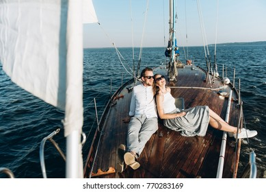 Young beautiful couple is resting on the sea, floating on a wooden yacht with sails. They sit on the yacht, laugh and look at the sunset