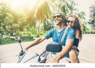Young beautiful couple rides the jungle on a scooter, travel, freedom, happiness, vacation, honeymoon concept