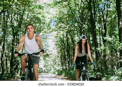 Young Beautiful Couple Riding Bike In Park