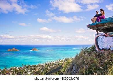 Young beautiful couple sitting on pillbox over looking Lanikai in Kailua Hawaii