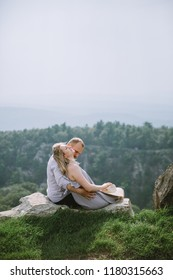 young beautiful couple sitting on the edge of mountains with a fantastic view