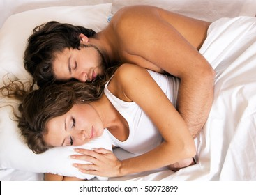 Young beautiful couple sleeping in bed