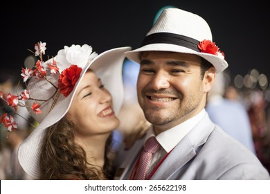 young beautiful couple smiling and laughing while wearing flower hats at the Dubai World Cup Horse Race
