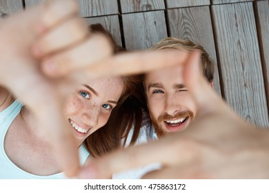 Young beautiful couple smiling, lying on wooden boards making frame with hands. Focus at faces.