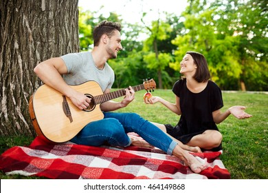 Young beautiful couple smiling, resting on picnic in park.