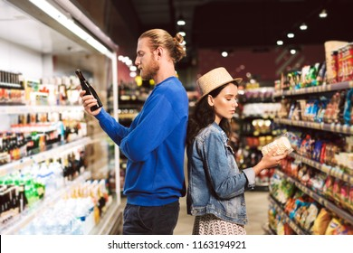 Young beautiful couple standing back to back thoughtfully choosing products spending time in modern supermarket