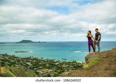 Young beautiful couple standing on a cliff while hiking the Instagram famous Pillbox trail over looking Lanikai in Kailua Hawaii