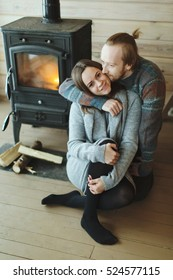 Young beautiful couple in sweaters in a country house sitting on the wooden floor near fireplace and kissing