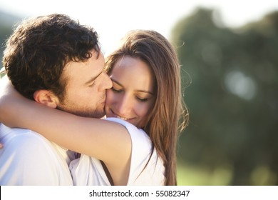 Young beautiful couple in a sweet cheek kiss