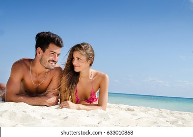 young beautiful couple taking sun at the beach