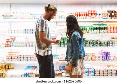 Young beautiful couple thoughtfully choosing milk together in dairy department of modern supermarket