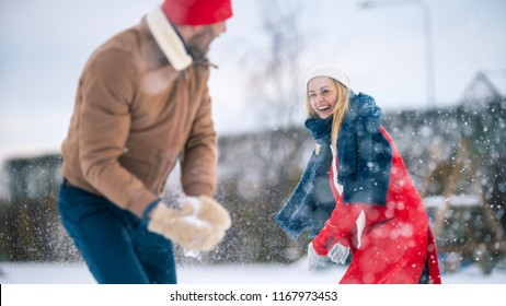 Young Beautiful Couple Throws Snow at Each other While Snow Falls. Happy Man and Woman Playing with Snow in the Yard of their Idyllic House. Family Enjoying Winter.
