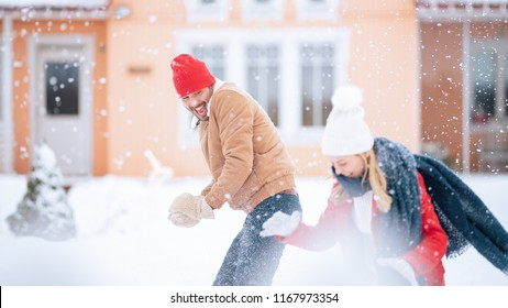 Young Beautiful Couple Throws Snowballs at Each other While Snow Falls. Happy Man and Woman Playing with Snow in the Yard of their Idyllic House. Family Enjoying Winter.