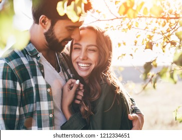 Young beautiful couple walking outside on beautiful sunset. Perfect romantic landscape for lovestory. Two hipsters-lovers hugging.