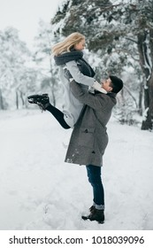 A young beautiful couple is walking in the winter park, hugging and having fun. A love story and Valentine's Day concept.