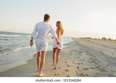 Young beautiful couple walks along the seashore at sunset. Honeymoon. Romantic trip.