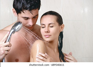 Young beautiful couple washing in the shower