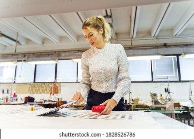 Young beautiful creator female entrepreneur at work - Beautiful woman choosing color from palette for new design in day at factory or studio front view- Business and creativity concept