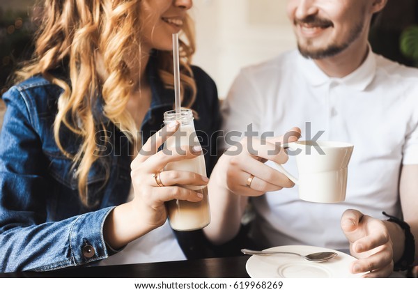 Young beautiful curly blonde bride Couple in love with hipsters In a cafe with a milkshake with a straw In a denim jacket