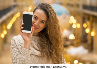 Young beautiful curly blonde woman showing your smart phone screen, golden indoor