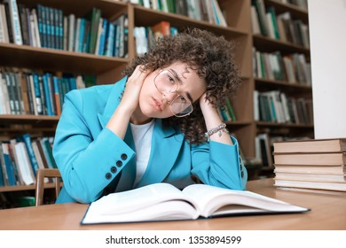 Young beautiful curly girl in glasses and blue suit sitting with books in the library. Student Study