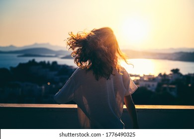 Young beautiful curly woman enjoys life in the summer sun, in motion