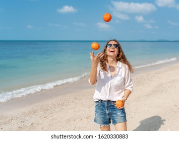 Young beautiful curly woman girl juggles oranges and has fun on a swing on a tropical beach. Vacation and travel concept.