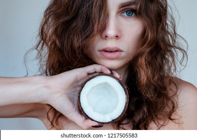 Young beautiful curly woman holding coconut. Skin and hair care concept