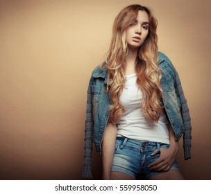 Young beautiful curly woman posing  over yellow background