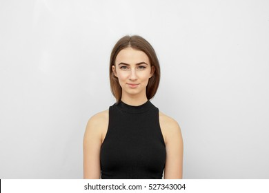 Young beautiful cute girl showing different emotions. Background for the girl a concrete gray wall. Laughing, smiling, anger, suspicion, fear, surprise.