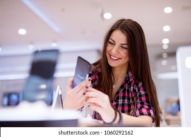 Young beautiful cute girl is trying out the display phone in a bright phone store.