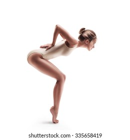 young beautiful dancer in beige swimsuit posing on a isolated white studio background