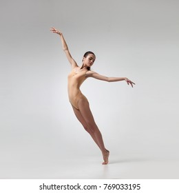 young beautiful dancer in beige swimsuit posing on light grey studio background