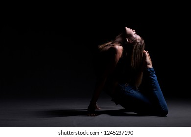 Young beautiful dancer in blue jeans posing on a dark studio background