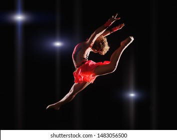 Young beautiful dancer gymnastics jumping in studio over black background