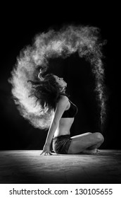 young beautiful dancer with hair movement on a dark studio background