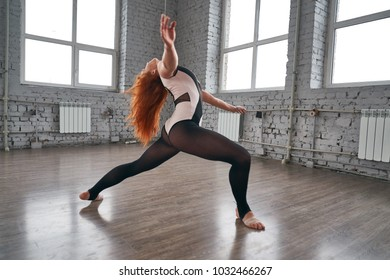 Young beautiful dancer posing on a studio background. Woman dancer in the gym.